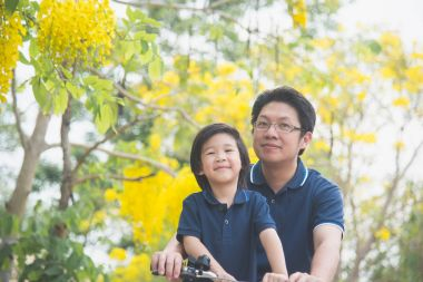 Asian  father and son riding bicycle