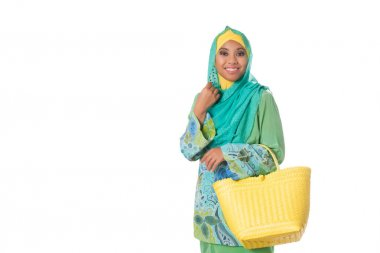 Asian muslimah woman with yellow wicker tote bag.Isolated.Copyspace