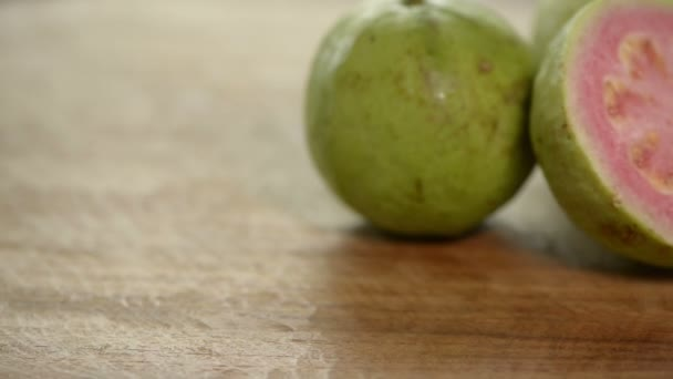 Cut pink guava rotates on wooden table