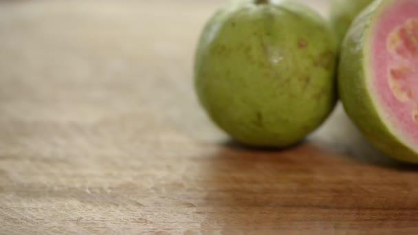 Přestřihl růžové guava otáčí na dřevěný stůl