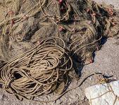 Staré rybářské sítě. Stočené a svázané v balíku na hrubé dřevěné pozadí staré lano