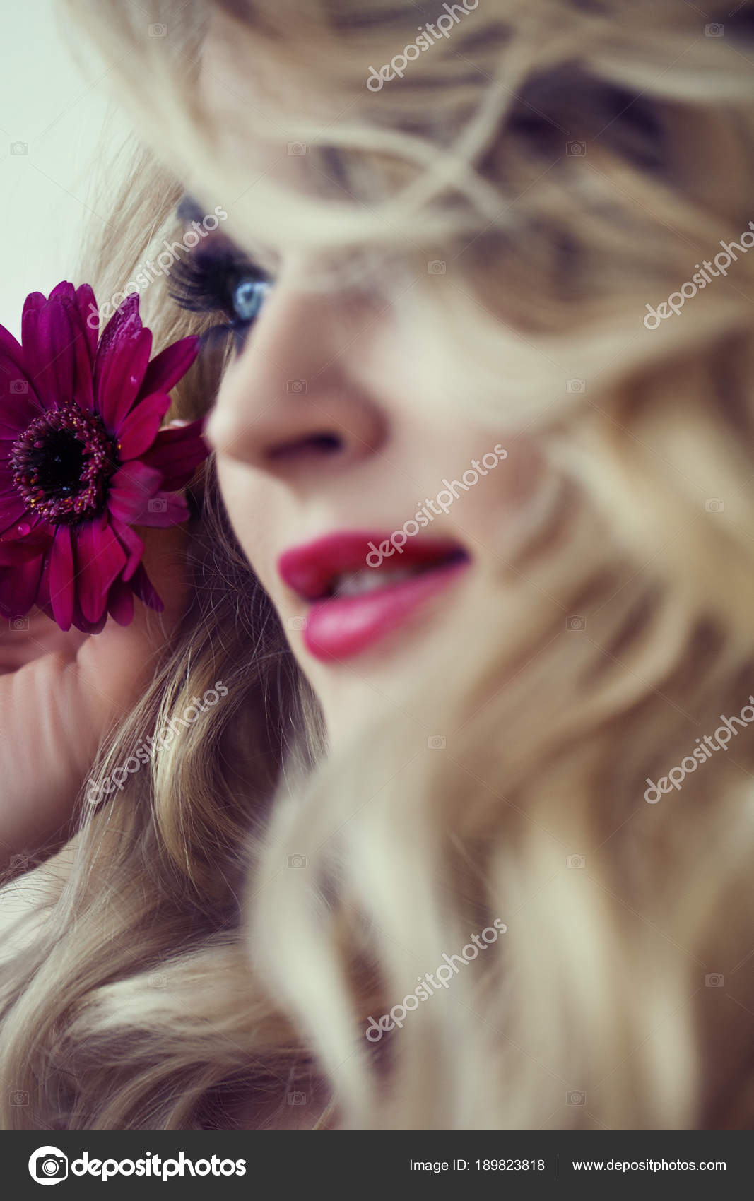 Beautiful Blonde Model Girl With Long Curly Hair And Red Flower