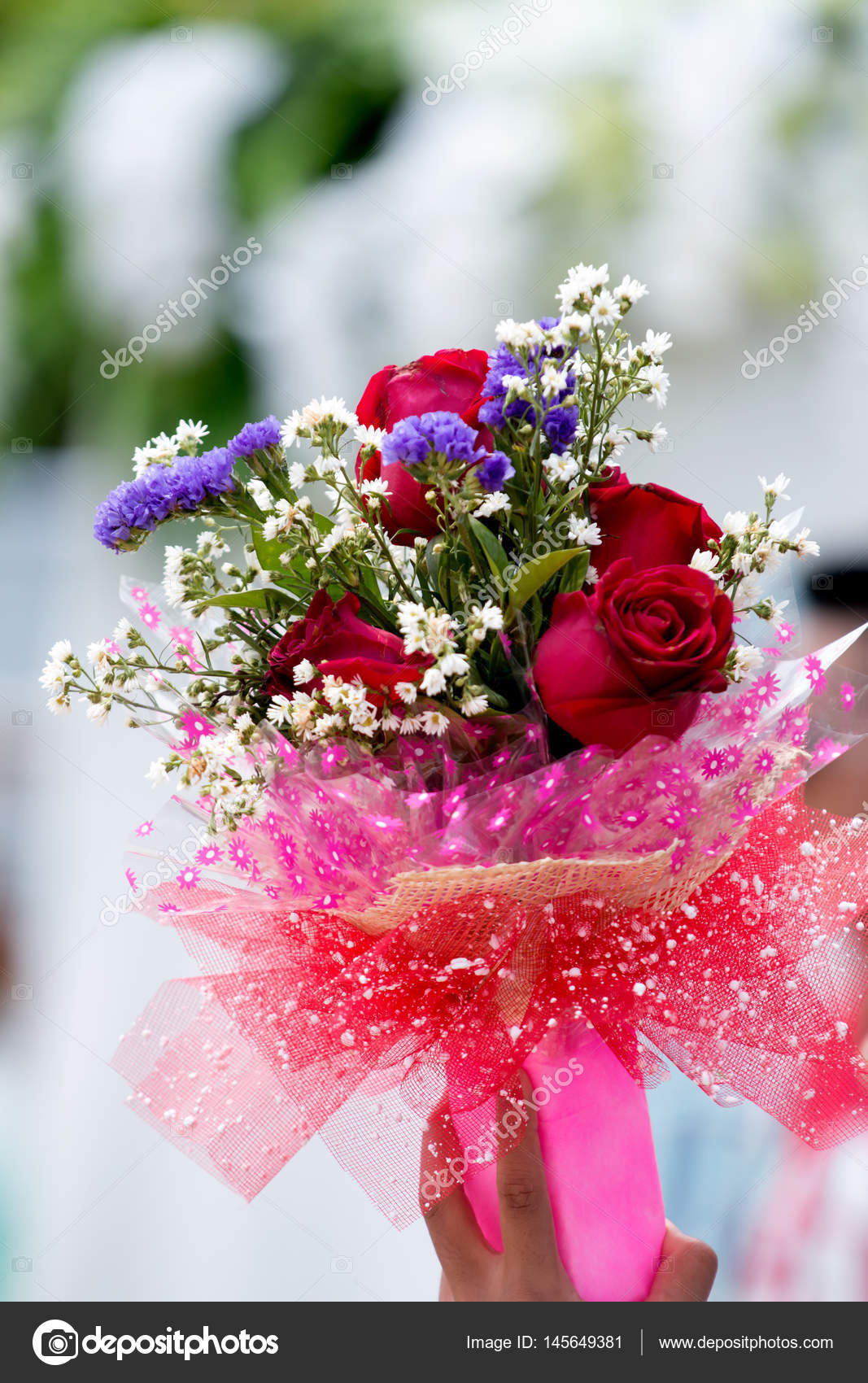 Bouquet of flowers in hand — Stock Photo © Tanagron #145649381