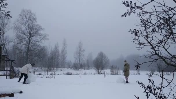 Šťastné děti dělají sněhuláka na zasněženém poli na venkově