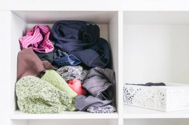 Home wardrobe with different clothes. Small space organization. The contrast of order and disorder. Vertical storage.