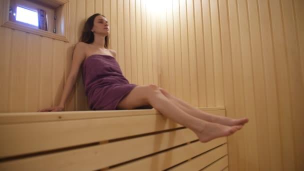 Mladá žena sedí na dřevěné lavičce v sauně.Krásná žena relaxovat v sauně a zůstat zdravý