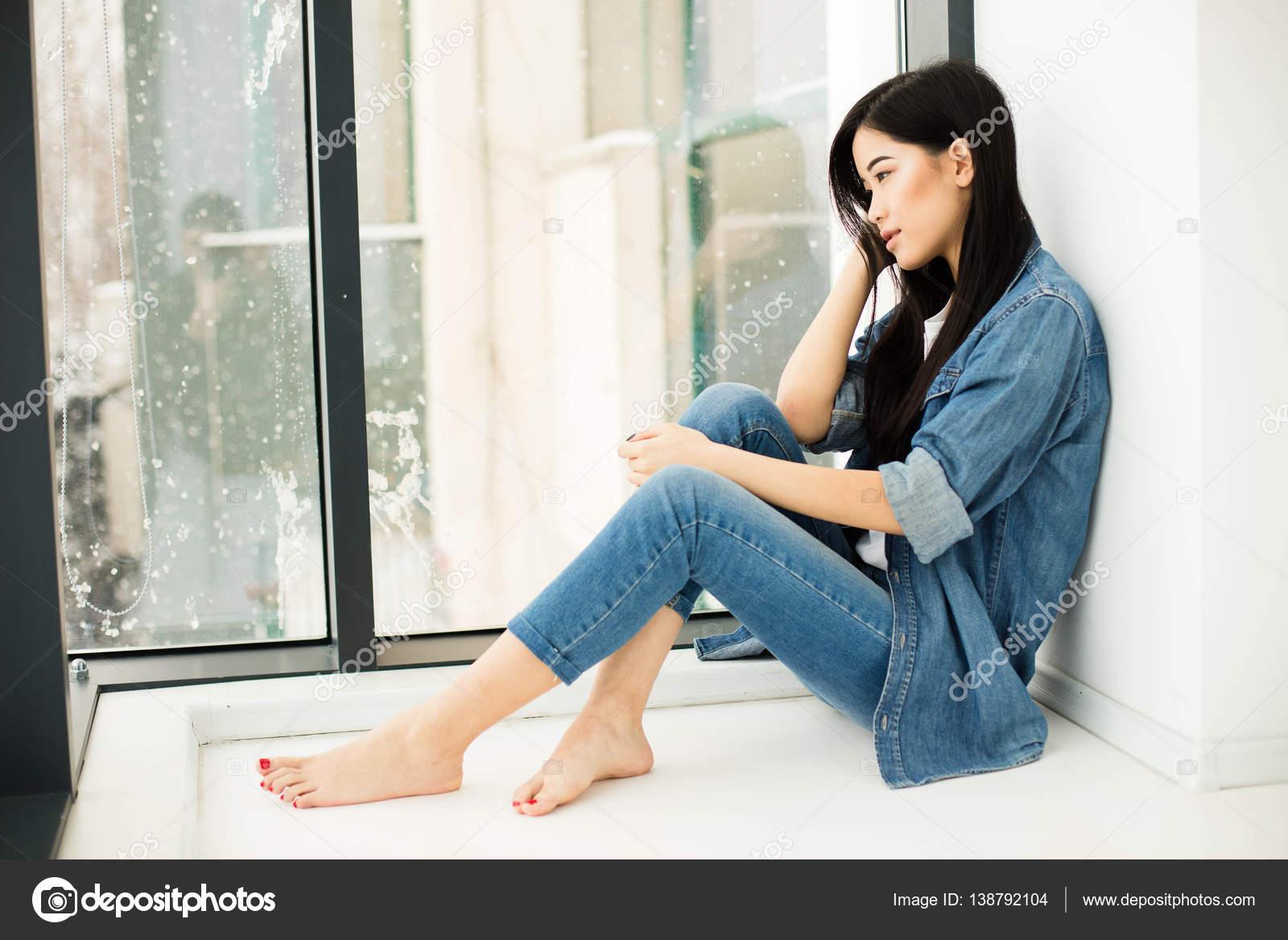 Chica Sentada En El Suelo Al Lado De Una Ventana