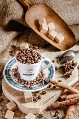 Rustic style, beautiful cutting boards, coffee cups with saucers, with an inscription of Lavazza coffee, on sacking, next to coffee beans, tubby, cinnamon and an old metal spoon