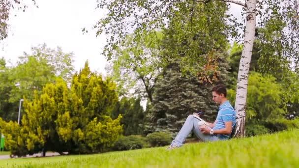 univerzitní student studuje na zkoušky venku v parku. s ním jeho knihy, zápisník, batoh a káva