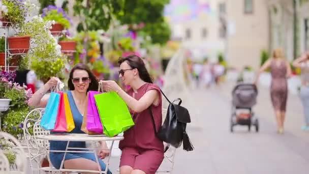 Két divat vásárlók nő, táskák, bevásárló az utcán. Eladó, a fogyasztás és a nép fogalmát. Kaukázusi lányok élvezik a meleg nap, szabadtéri kávézó.