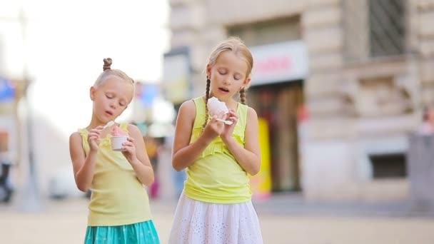 Rozkošné holčičky jíst zmrzlinu venku v létě. Roztomilé děti těší skutečné italské gelato poblíž Gelateria v Římě