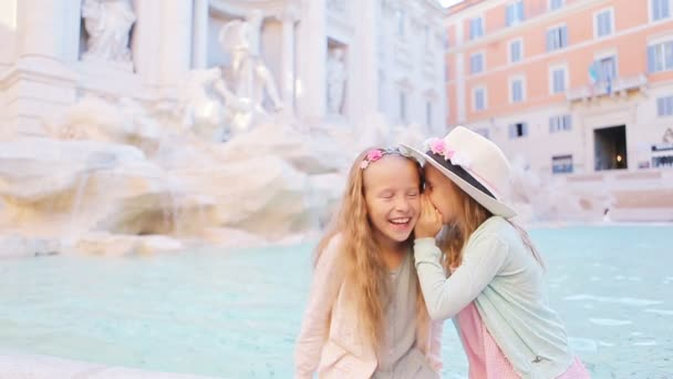 Adorable little girls whispering sitting on the edge of Fountain of Trevi in Rome. Happy kids enjoy their european vacation in Italy