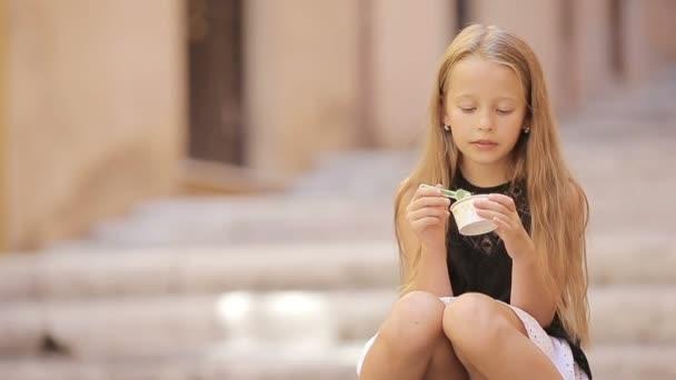 Rozkošná holčička jíst zmrzlinu venku v létě. Roztomilé dítě těší skutečné italské gelato v Římě