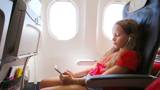 Rozkošná holčička, která cestuje letadlem a sedí u okna. Kid poslech hudby a posílání zprávy sedí u okna letadla