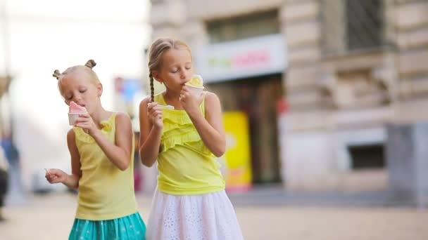 Roztomilé dívky jíst zmrzlinu venku v létě. Roztomilé děti těší skutečné italské gelato poblíž Gelateria v Římě