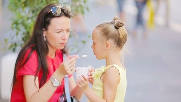 Giovane madre e le sue figlie che mangia il gelato allaperto. Mamma nutre la sua figlia gelato in strada