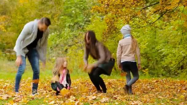 Mladý, usměvavý, rodinné házel listí kolem na podzimní den venku