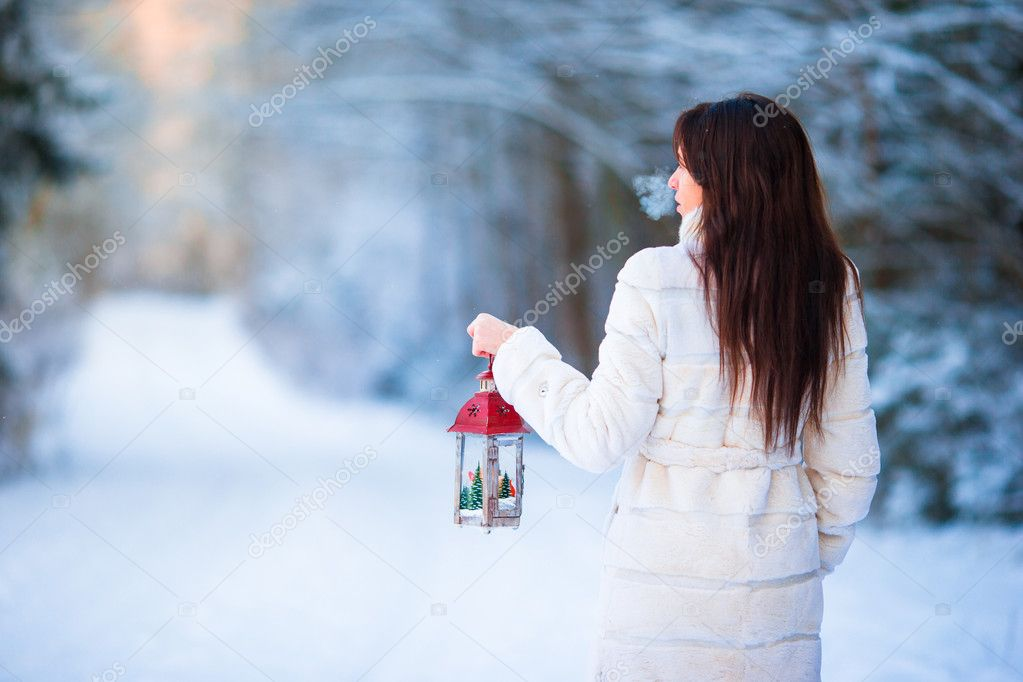 Winter beauty. Woman holding Christmas lantern outdoors on beautiful winter snow day