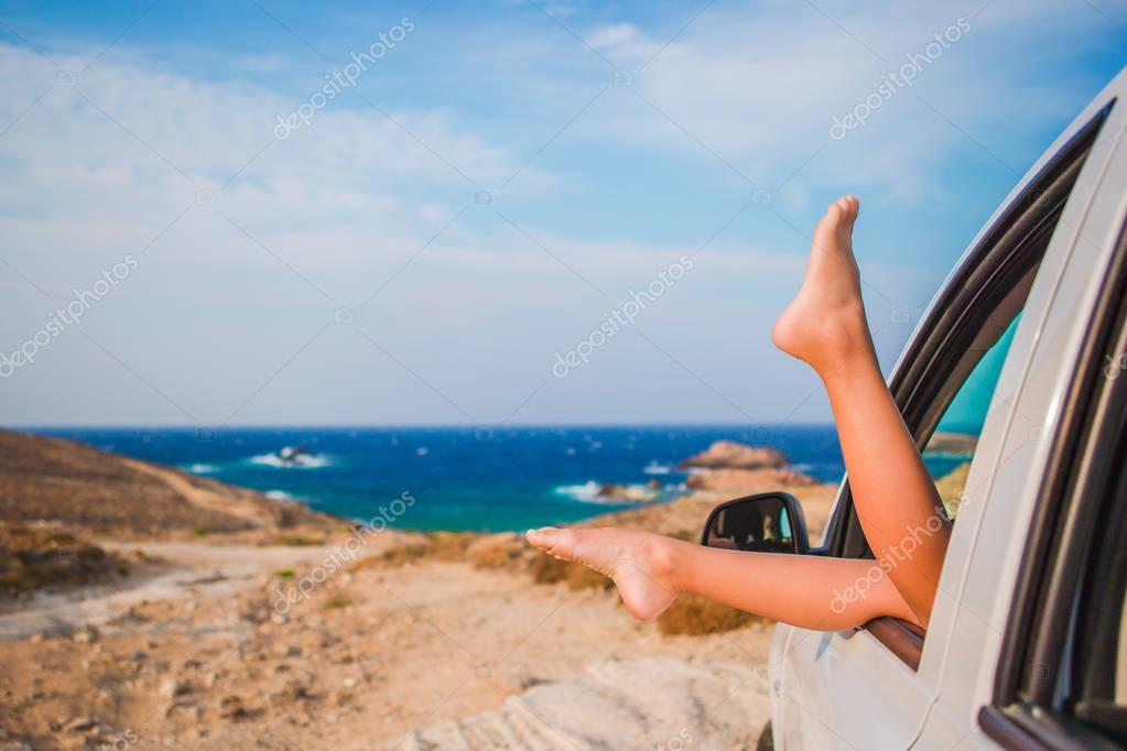 Summer vacation, holidays, travel, road trip and people concept - close up of little girl feet showing from car window