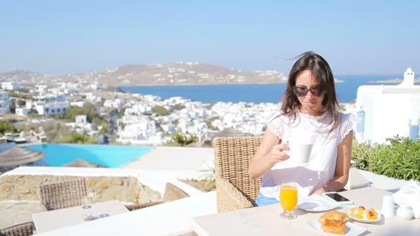 Krásná elegantní dáma snídáš ve venkovní kavárně s úžasným výhledem na město Mykonos. Žena pít horké kávy na luxusní hotelové terase s výhledem na moře v rezortu restaurace