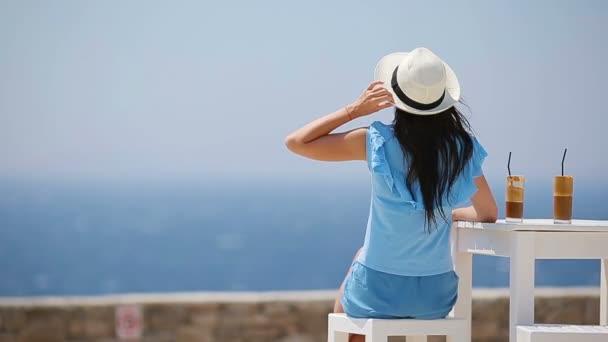Mladá žena pije studenou kávu s výhledem na moře. Krásná žena relaxovat během exotické dovolené na pláži těší frappe