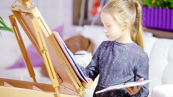 Imádnivaló kislány festeni egy képet festőállvány beltéri