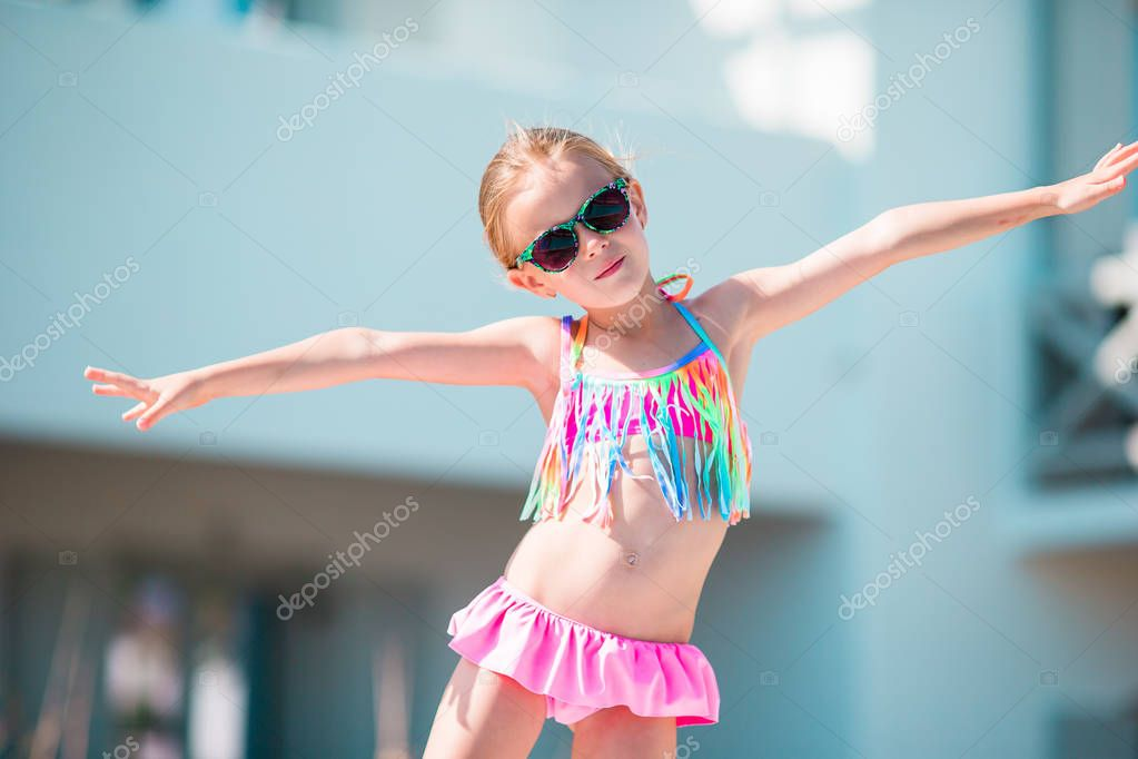 Portrait of adorable smiling little girl on beach vacation