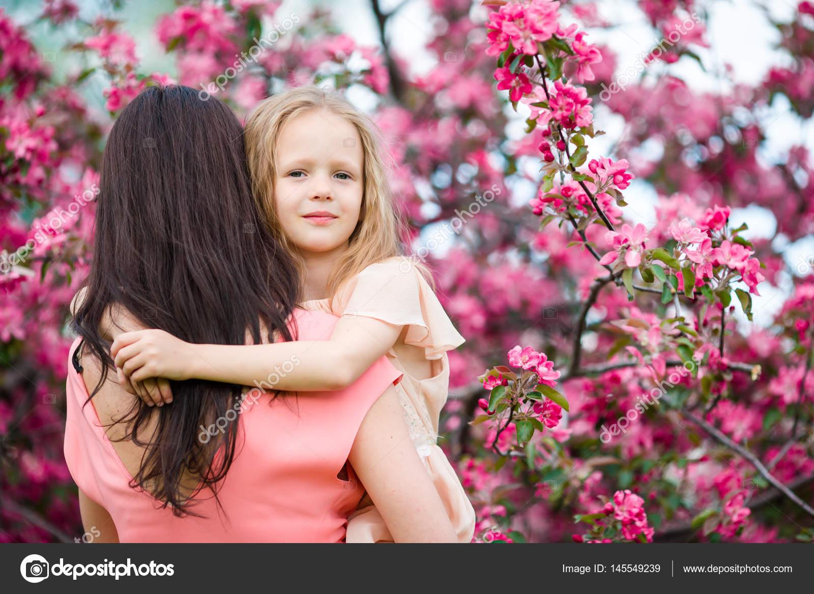 Adorable niña con jardín de joven madre en floración cerezos en ...