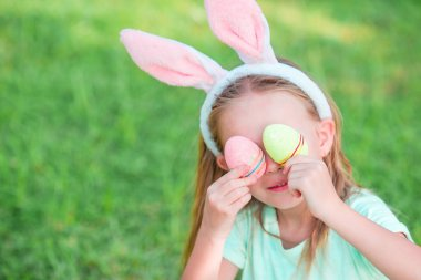 Adorable little girl wearing bunny ears with Easter eggs on spring day