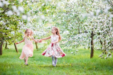 Beautiful girls in blooming apple tree garden enjoy warm spring day