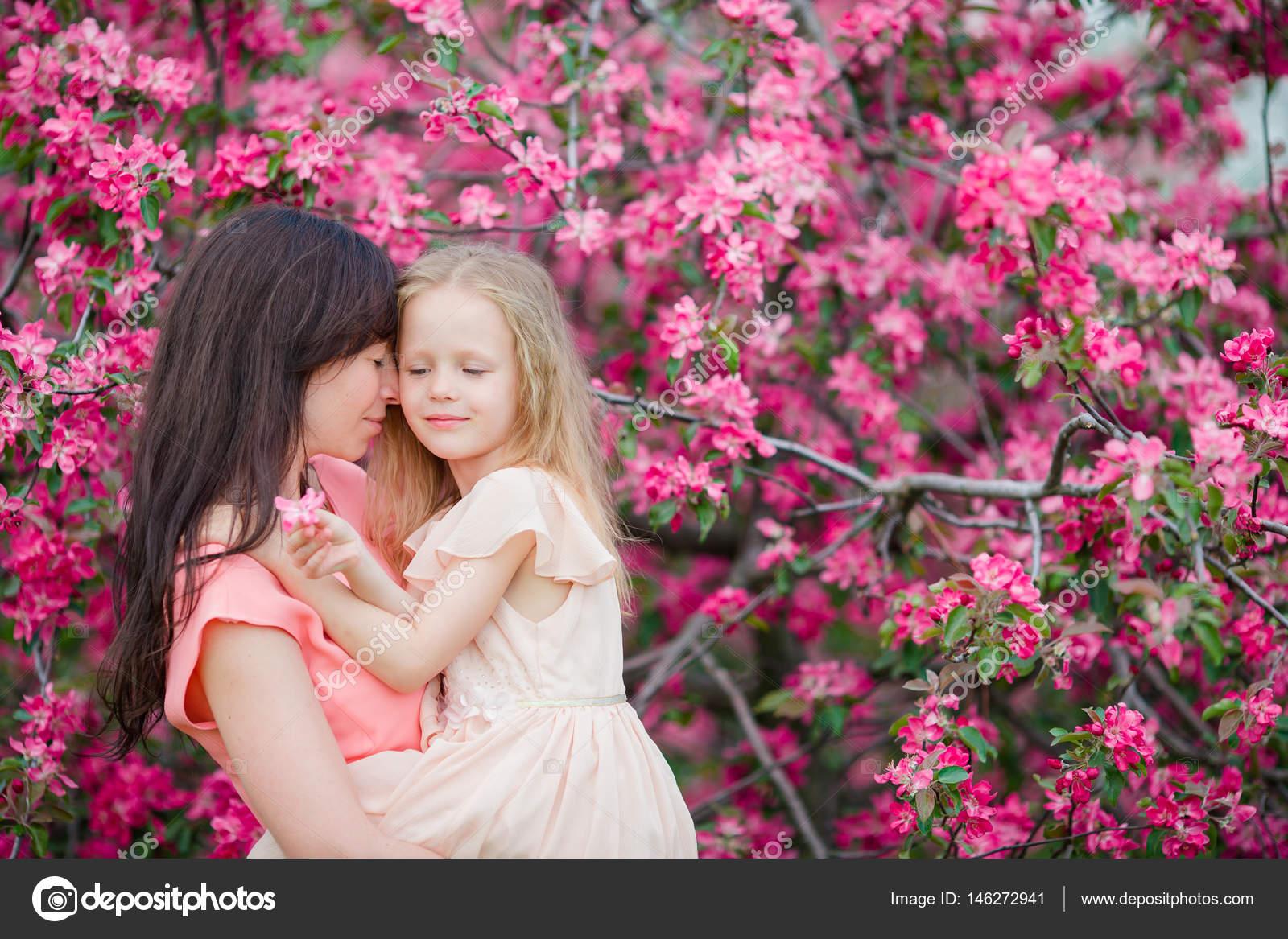 Familia de mamá y niño en jardín florido día de hermosa primavera ...