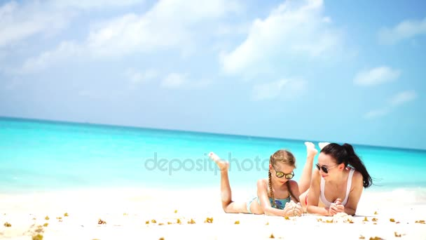 Little adorable girl and young mother at tropical beach