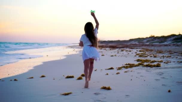 Rozkošná holčička s létání draka na tropické pláži mají spoustu zábavy. Děti hrají na břehu oceánu s plážové hračky