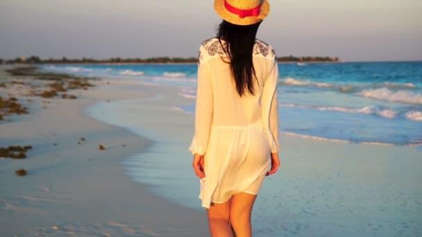 Krásná žena na letních prázdnin na bílé pláži. Šťastná dívka v letních šatech. Zpomalený pohyb