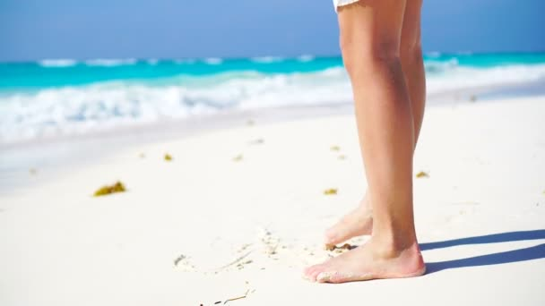 Close-up legs walking along the white beach in shallow water. Concept of beach vacation and barefoot. No shoes no news