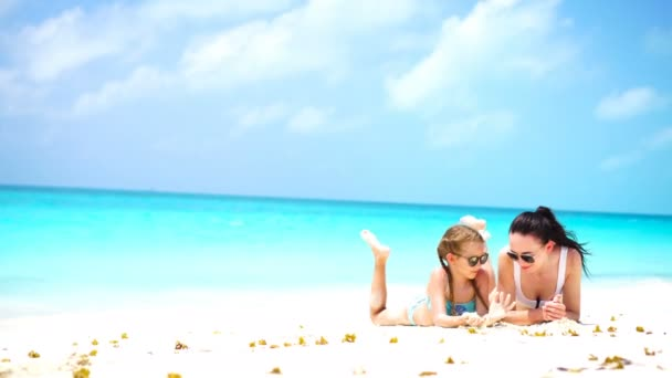 Little adorable girl and young mother at tropical beach lying on white beach and enjoy their summer vacation