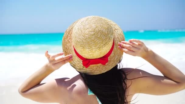 Back view of beautiful woman in hat on summer holidays on white beach.