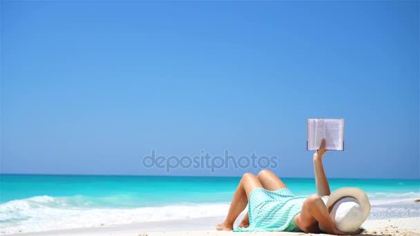Mladá žena čtení knihy během tropických bílá pláž