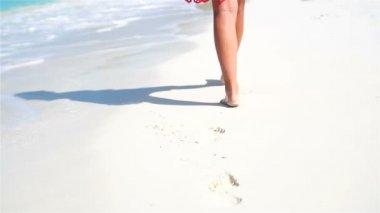 Női lábak fut végig a fehér strand sekély vízben. Koncepció, tengerparti nyaralás, és mezítláb. Lassú mozgás