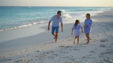 Family have fun on white beach on caribbean island in the evening