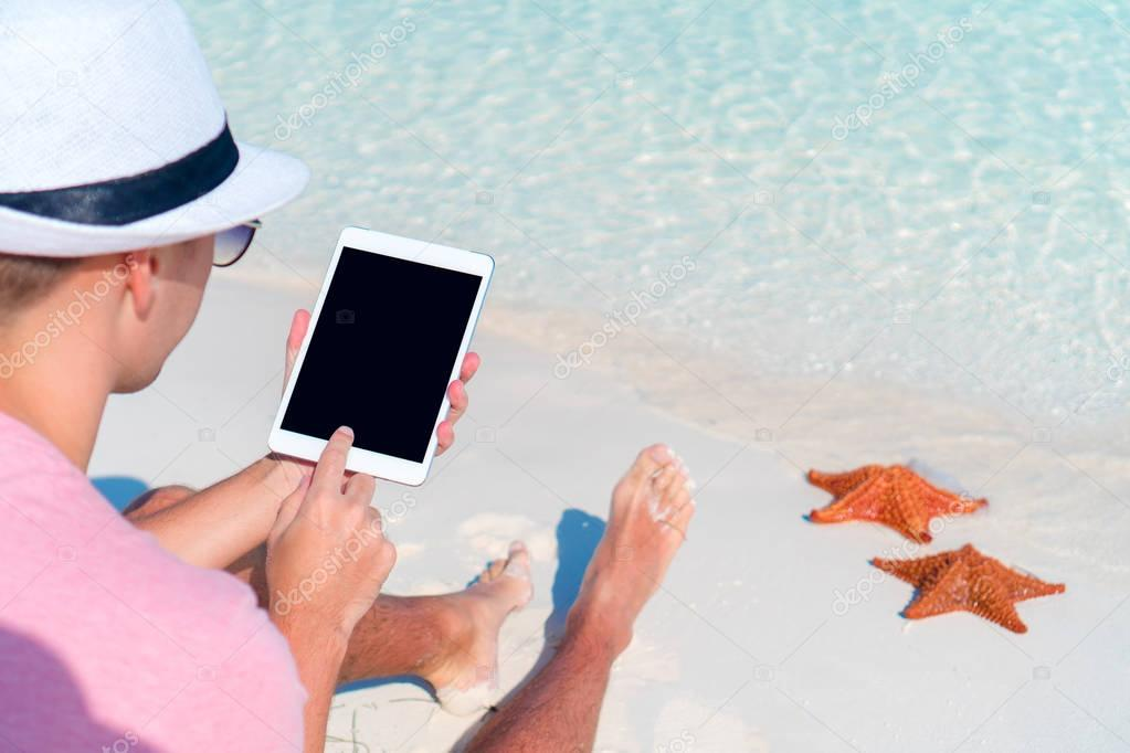 Young man with laptop on the background of turquoise ocean at tropical beach take a photo of starfish in natural reserve