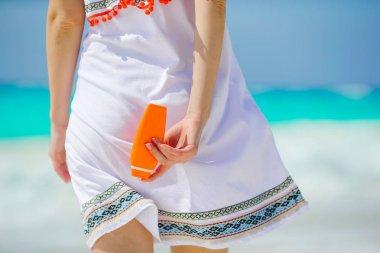 Suncream bottle in female hands background the sea. Suncare concept.