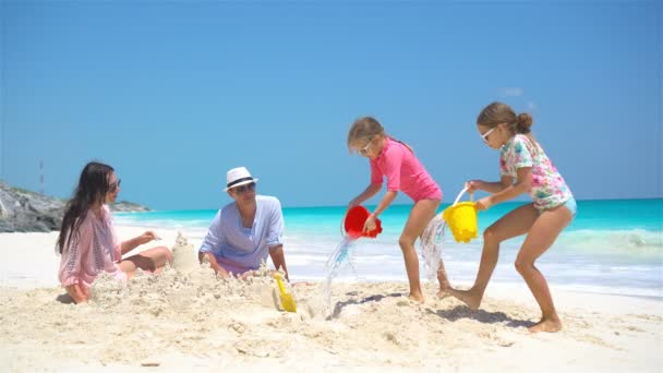 Family with two kids making sand castle at tropical beach