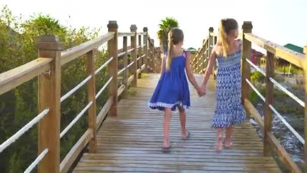 Rozkošné holčičky na dřevěný most na cestě do bílého tropické pláže a tyrkysové moře