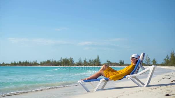 Relaxační lehátko na tropické pláži mladá žena