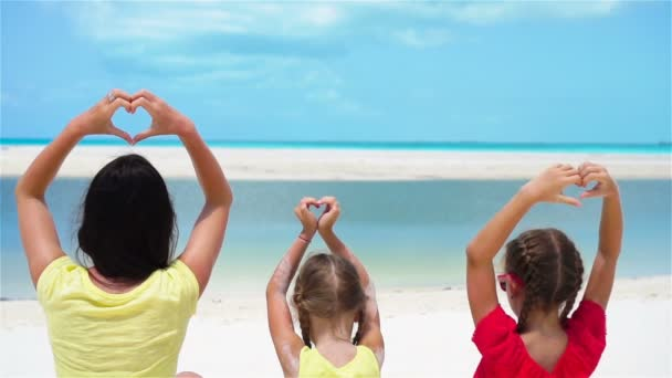Adorable little girls and young mother showing hearts on white beach. SLOW MOTION