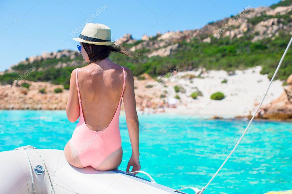 Фотообои Beautiful young woman relaxing on the boat in amazing turquoise lagoon on Sardinia