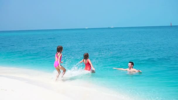 Happy family at tropical beach have fun. Father and little kids enjoy time together swimming in the sa. SLOW MOTION