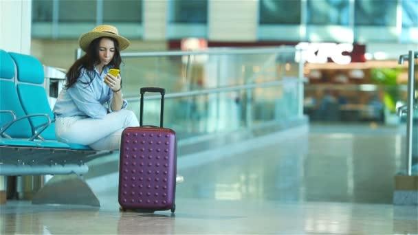Mladá žena v letištní hale čeká na letu letadla. Kavkazský žena s smartphone v čekárně