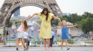 Happy family of mother and kids in Paris near Eiffel tower. French summer holidays, travel and people concept. European vacation